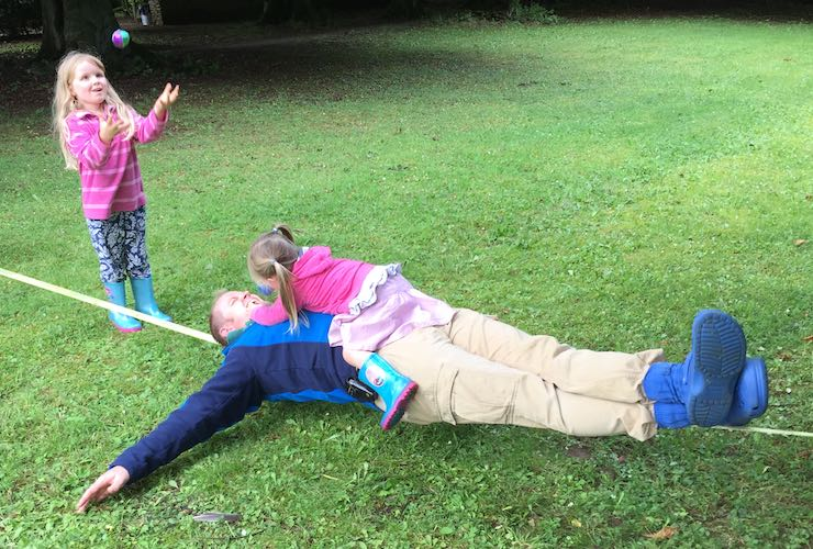 Dad lying over a tightrope with daughter lying on top of him