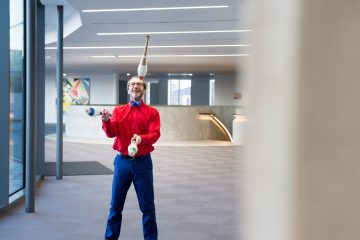 Stuart Priest juggling with clubs inside a corporate hallway