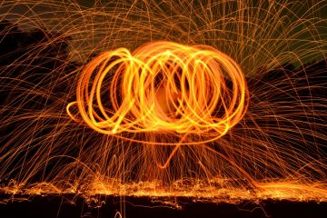 Steel wool poi lit up like fire against a black background
